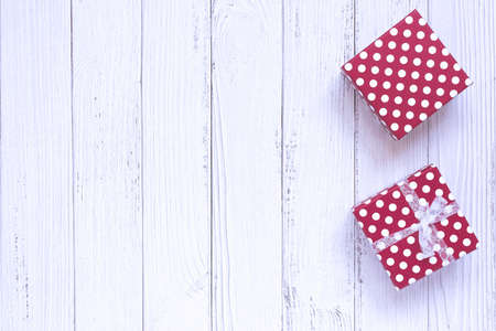 Top view of gift boxes wrapped in red dotted paper over white wood background. Copy space, flat lay. Holidays concept. 写真素材