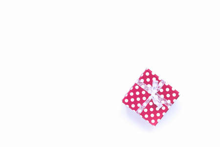 Top view of a gift box wrapped in red dotted paper over white background. Copy space, flat lay. Holidays concept.