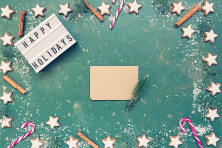 Christmas composition, empty greeting card, candy canes, cookies and light box with text Happy holiday on green vintage background. Christmas, winter, new year concept. Flat lay, top view, copy space.