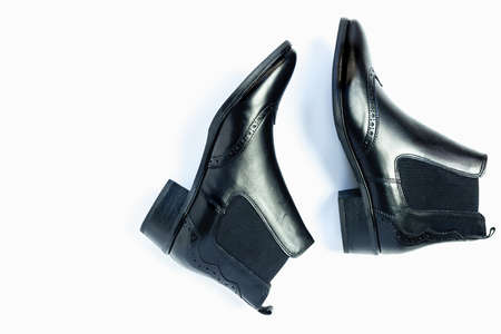 Close up of a womens black leather chelsea boots on white background with reflection. Womens footwear for city, urban lifestyle or traveling. Concept of fashion, design and footwear. 写真素材 - 134967764