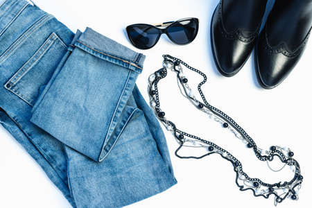 Overhead view of womans casual outfit on white background - glasses, blue jeans, necklace and leather chelsea boots. Flat lay, top view, copy space. Trendy, minimal hipster look. 写真素材 - 134967766