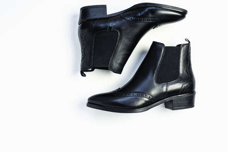 Close up of womens black leather chelsea boots on white background with reflection. Womens footwear for city, urban lifestyle or traveling. Concept of fashion, design and footwear.
