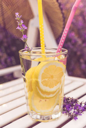 Glass of fresh lemonade over white wooden chair in lavender field