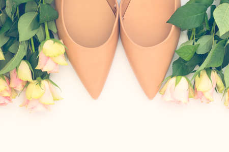 Pair of stylish pastel beige women shoes and roses on white background. Flat lay, top view trendy fashion feminine background. Beauty blog concept.
