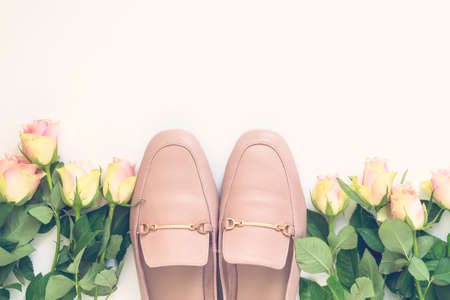 Pastel pink women shoes and roses on white background. Pair of elegant and stylish loafers. Flat lay, top view trendy fashion feminine background. Beauty blog concept.