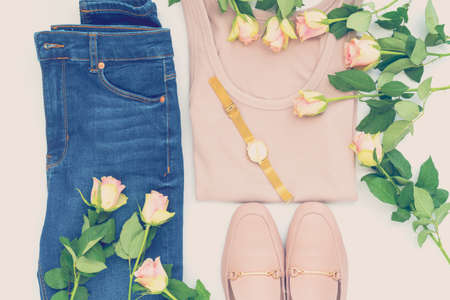 Flatlay of women's stylish outfit and roses on white bacground. Trendy clothes collage. Minimal and beauty blog concept