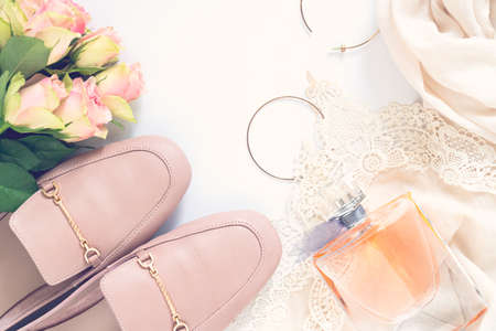 Pastel pink women shoes, perfume and roses on white background. Pair of elegant and stylish loafers. Flat lay, top view, romantic fashion feminine background. Beauty blog concept.