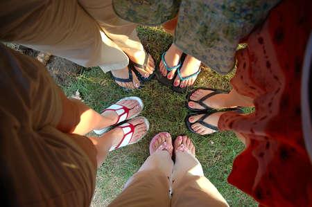 夏の足 - 十代のガール フレンドのグループ塗装足指の爪と夏のサンダルを示すハドルで立っています。 写真素材