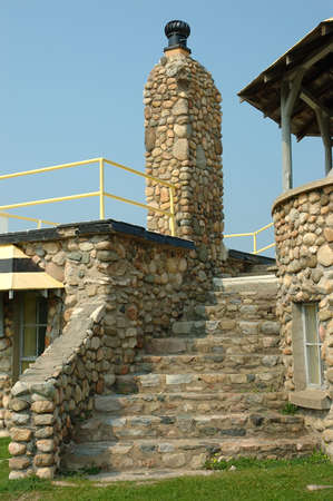 Stone Stairway - A stone stairway leads to the rooftop of a rock and stone house. Stock Photo