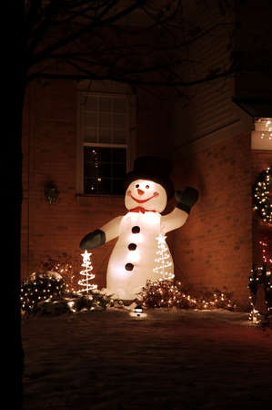 Inflatable snowman stands in the corner with holiday christmas lights.