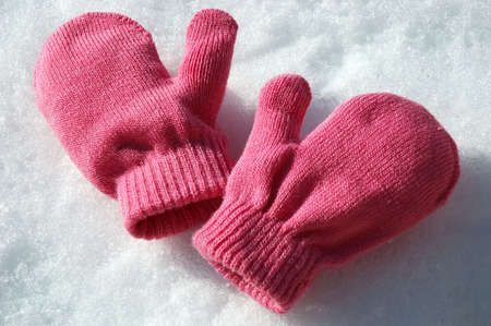 Pink knit mittens laying on the snow.