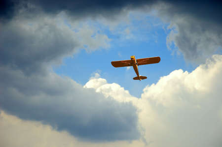 A piper airplane appears through the hole in the clouds on a stormy day.