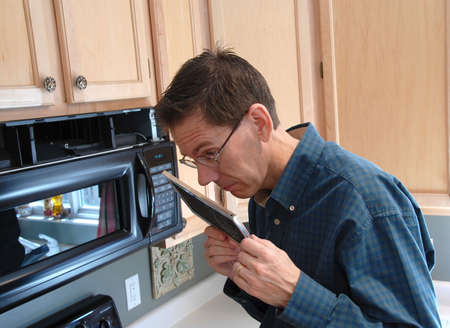 Man smelling the old filter that he just removed in a microwave in the kitchen of a modern home.