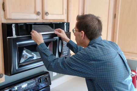 Man replacing the filter in a microwave in the kitchen of a modern home. Imagens - 394563