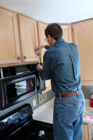 Man using a screwdriver to repair his microwave in the kitchen of a modern home. Imagens - 394581