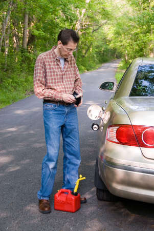 Upset man  on a country road, staring into his wallet while a gas can is at his eet.  Will he be able to pay for the gas for the empty gas tank of his car? Stock Photo - 394592