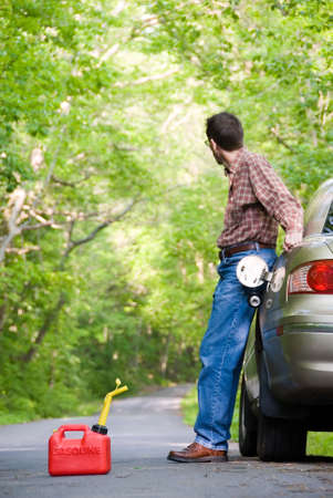 A man is stranded on a country road, his car is out of gasoline and hes staring down the road looking for help.  Focus is on the gas can. Imagens