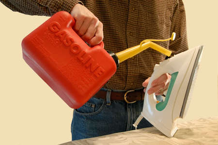 A man pouring gasoline into his clothes iron from a gas can.  Humorous concept image.