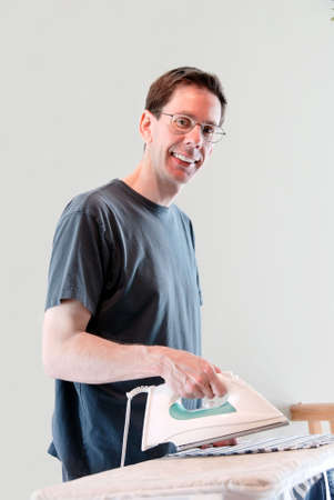 A very happy, smiling man doing his own laundry and ironing his clothes. Imagens