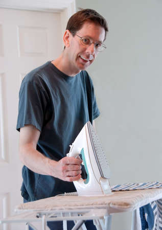 A smiling man doing his own laundry and ironing his clothes.