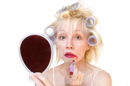 A blonde woman with lavender curlers in her hair received shocking news as she is applying her lipstick.  Smeared lipstick on her face and surprise in her eyes.