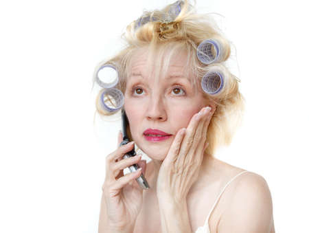 A blonde woman with lavender curlers in her hair is talking on her cell phone and making a face.