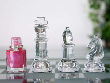 Chess set pieces with the Queen represented by a bottle of pink nail polish and a 2 carat princess cut diamond ring.