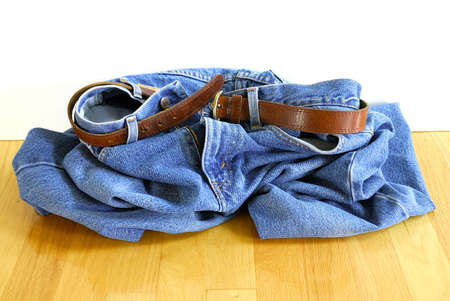 Drop Your Jeans - a pair of blue jeans with a leather belt is in a heap on the floor.