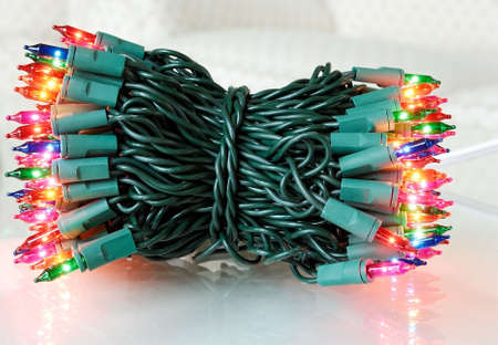 A colorful bundle of christmas tree lights on a reflective surface.