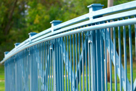 Blue Fence with a green background. Shallow depth of field. Archivio Fotografico