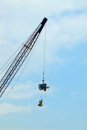Hows It Hangin? - A crane lifts expensive construction equipment overhead to ward off theft.
