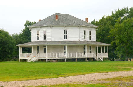 White Octagonal Farmhouse - an old country farmhouse with six sides and several entrances.  Stock Photo