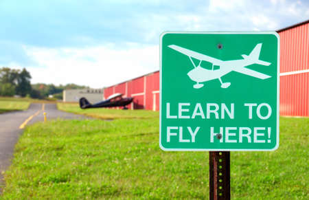 Airport Sign - Learn To Fly Here - a sign at a small airport in front of the hangars.
