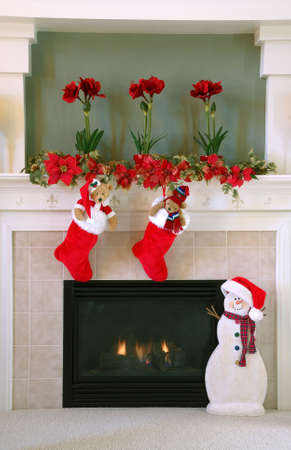 Christmas Decor at Home - Red and white fur christmas stockings with stuffed bears inside hang on the mantle above the fireplace on Christmas.