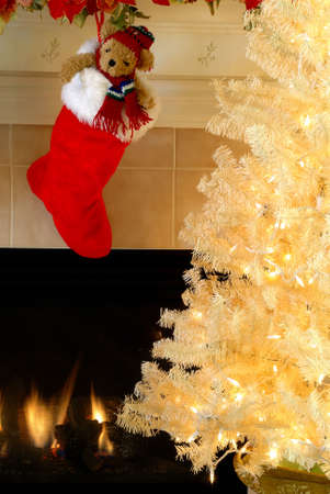 Christmas Eve - Red and white fur christmas stocking with a stuffed bear inside hangs on the mantle above the fireplace on Christmas Eve while a vintage white christmas tree sparkles in the night. Imagens - 670997