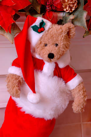 Santa Bear Christmas Stocking - Red and white fur christmas stocking with a stuffed bear inside hangs on the mantle above the fireplace. Imagens - 670993