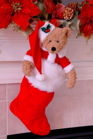 Santa Bear Christmas Stocking - Red and white fur christmas stocking with a stuffed bear inside hangs on the mantle above the fireplace. Imagens - 670992