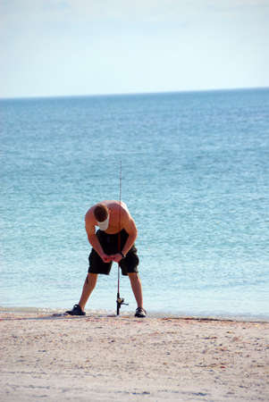A fisherman baiting his line to go fishing in the gulf of Mexico, Florida, USA. 免版税图像