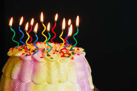 Lighted Birthday Cake - Burning candles on a pink and yellow iced birthday cake in front of a black background.  Imagens
