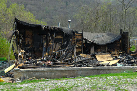 Burned, Fire Damaged Home - The charred ruins of a burned out trailer home in the hills of Kentucky, USA.