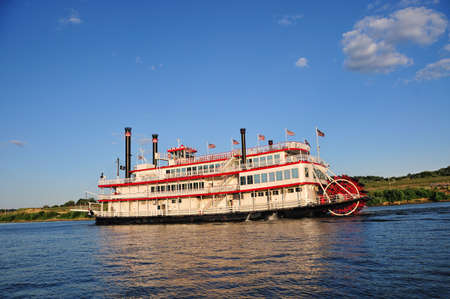 A paddle wheel boat cruising up the Ohio River on a warm summer day.
