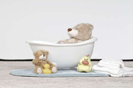 Papa Bear Takes A Bath - Plush bear toy in a baby bathtub with towels and bath toys on the floor.