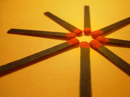 Group of red and black matches over a yellow background