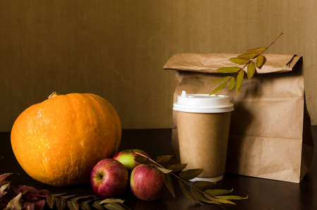 Paper bag, autumn leaves and hot steaming cup of coffee. Business lunch concept