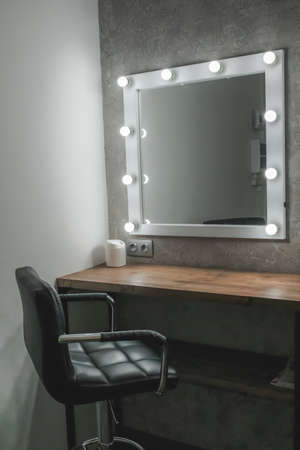 Interior of a beauty salon. Room with makeup mirror lights and black chair Standard-Bild
