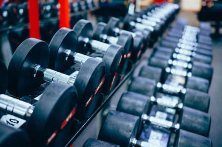 Rows of dumbbells in the gym. Concept of bodybuilding