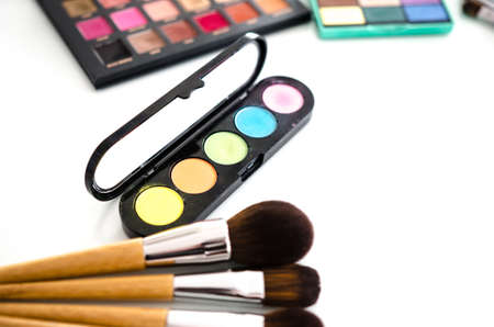 Makeup cosmetics on white table. Beauty tools palettes collection. Soft focus