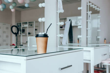 A cup of coffee near mirror on table in stylist room Banco de Imagens