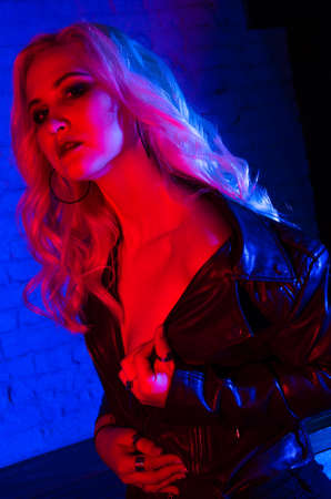 Fashion model woman in leather jacket. Portrait in colorful bright lights with trendy make-up
