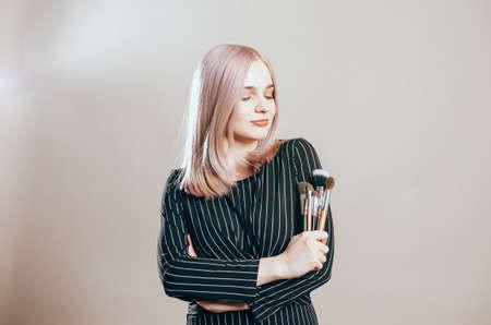 Beautiful blonde girl  in black dress. Beauty portrait of a joyful beautiful woman posing with make-up brushes on a beige background. Professional stylist Banco de Imagens